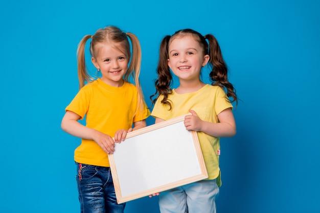 Dwie małe dziewczynki uśmiechnięte z pustą deską kreślarską na niebieskim tle