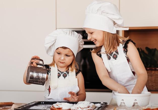 Dwie małe dziewczynki w białych czapkach szefa kuchni bawią się w kuchni. dzieci gotują jedzenie