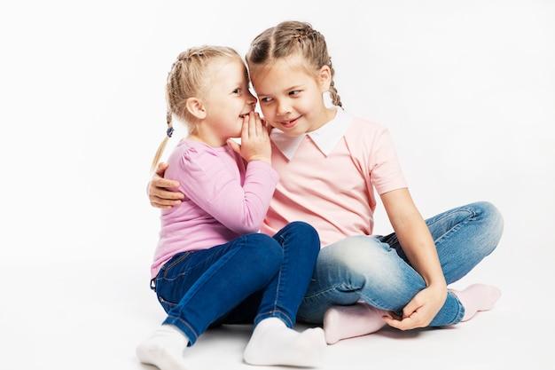 Dwie małe dziewczynki w dżinsach i różowych swetrach plotkują. biała ściana.