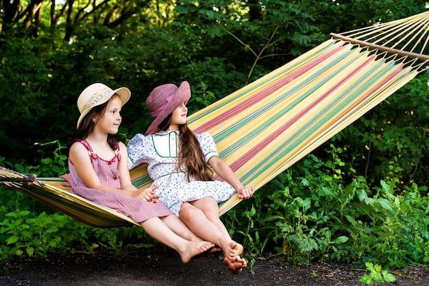 Dwie małe dziewczynki w kapeluszu siedzą na jasnym hamaku