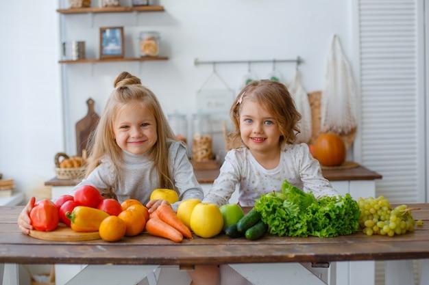 Dwie małe dziewczynki w kuchni z warzywami w domu