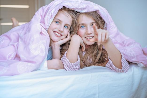Dwie małe dziewczynki w łóżku chowają się pod kołdrą.