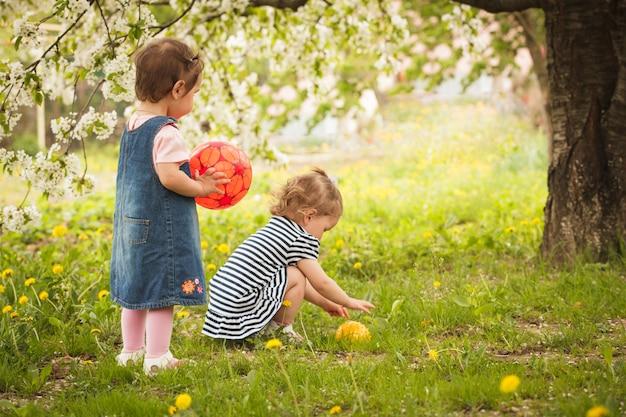 Dwie małe dziewczynki w parku pod kwitnącym drzewem, bawią się piłkami
