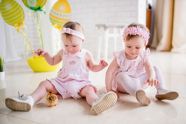 Dwie małe dziewczynki w różowych sukienkach bawią się na podłodze w studiu z wielkanocnym wystrojem