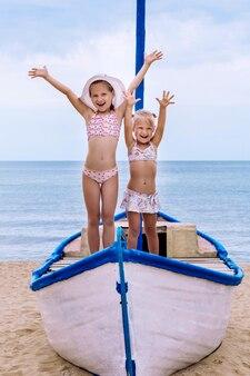 Dwie małe dziewczynki w strojach kąpielowych stoją w biało-niebieskiej łodzi na piasku na tle morza, podnosząc ręce do góry