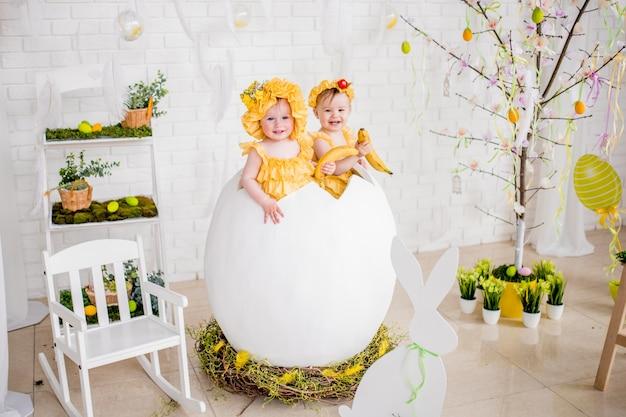 Dwie małe dziewczynki w żółtych sukniach siedzą w jajku w studiu