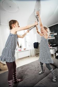 Dwie małe dziewczynki walczą na poduszki w sypialni