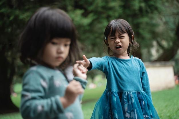 Dwie małe dziewczynki walczą o zabawki