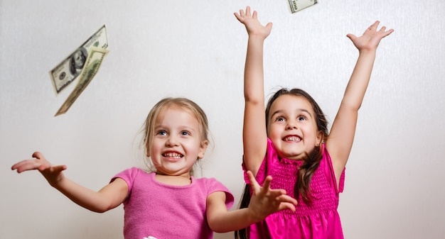 Dwie małe dziewczynki z dolarami