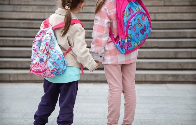 Dwie małe dziewczynki z pięknymi plecakami na plecach idą razem do szkoły ręka w rękę z bliska. koncepcja przyjaźni z dzieciństwa.