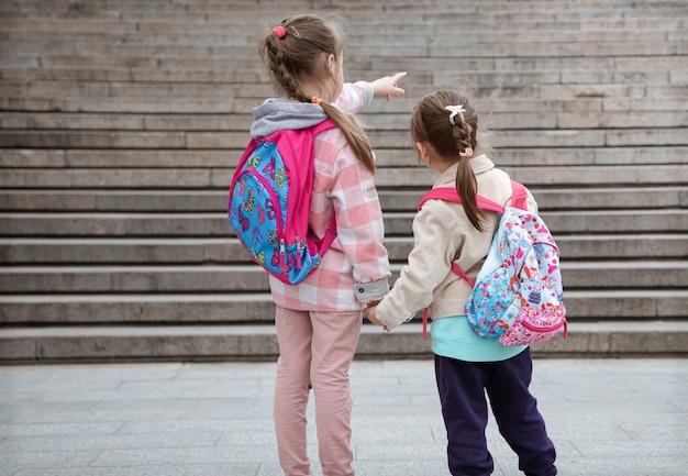 Dwie małe dziewczynki z plecakami na plecach idą razem do szkoły. przyjaźń z dzieciństwa