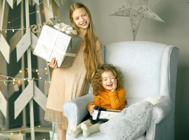 Dwie małe dziewczynki z prezentami stojące przy stylizowanej choince