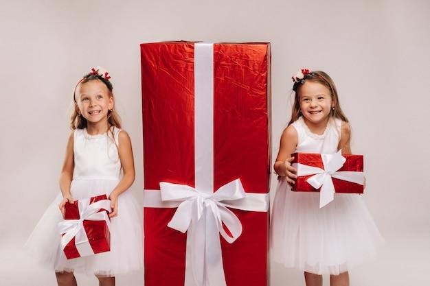 Dwie małe dziewczynki z prezentami świątecznymi na białym i wielkim prezentem.
