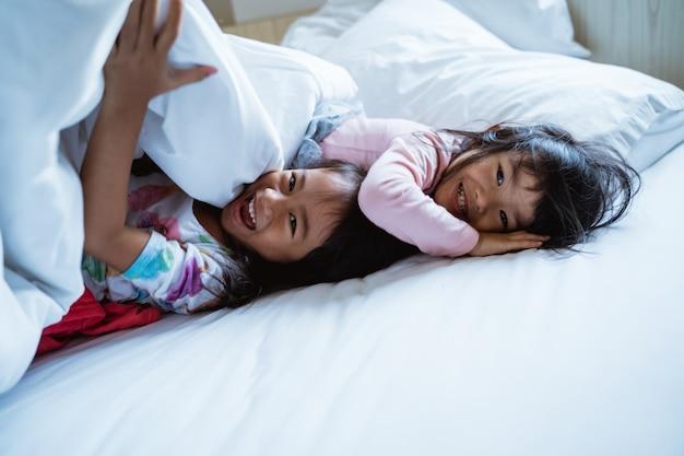 Dwie małe dziewczynki, zabawy i śmiechu w łóżku