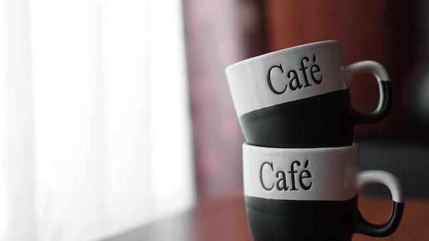Dwie małe filiżanki do kawy nad brązowym drewnianym stołem z rozmytym tłem