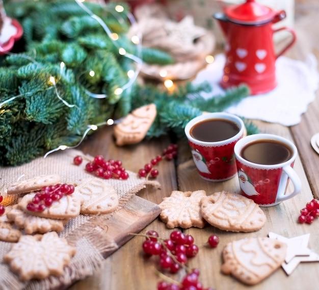Dwie małe filiżanki kawy i dzbanek do kawy, ciasto z jagodami i ciasteczkami, prezenty, w pobliżu choinki na wiejskim stole przy oknie