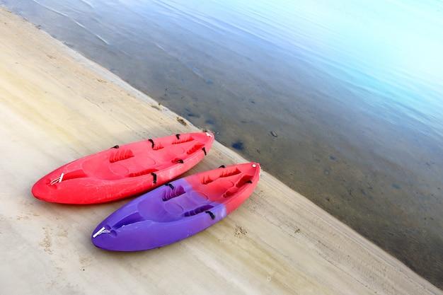 Dwie małe łodzie kajakowe w kolorze czerwonym i fioletowym na piaszczystej plaży ocean concept business life saver