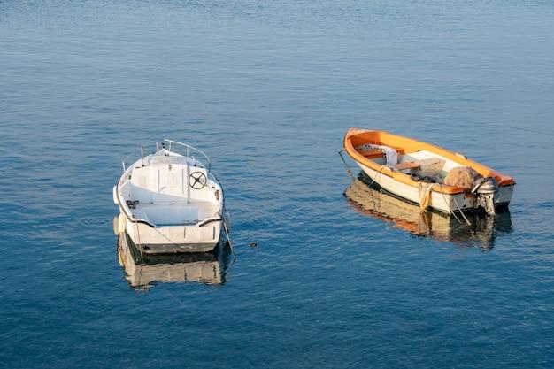 Dwie małe łodzie rybackie unoszące się na brzegu morza śródziemnego. włochy. pejzaż morski.