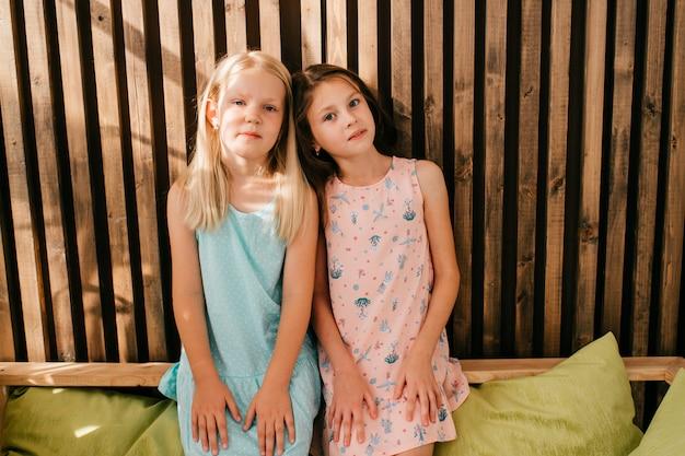 Dwie małe modelki w pięknych sukienkach siedzi na cytrynowym łóżku z drewnianą ścianą