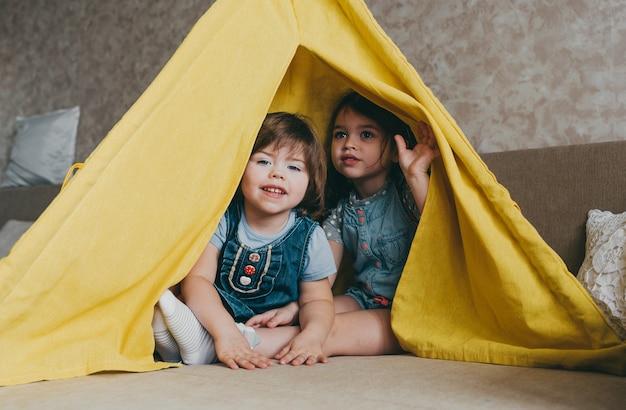 Dwie małe piękne dziewczynki bawią się w żółtym tipi