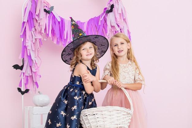 Dwie małe piękne słodkie dzieci dziewczyny w karnawałowych strojach czarownice i wróżki w halloween