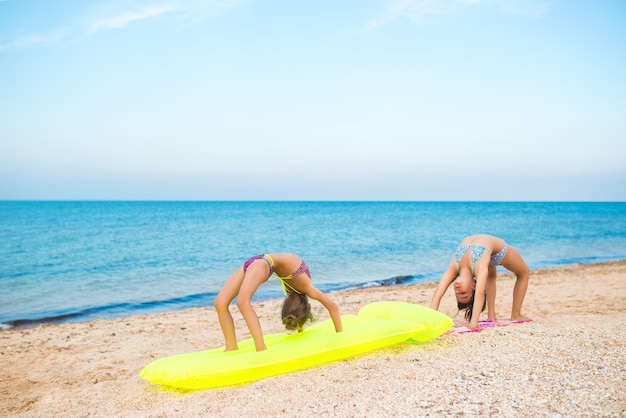 Dwie małe pozytywne dziewczynki gimnastyczki wykonują ćwiczenia, relaksując się na piaszczystej plaży