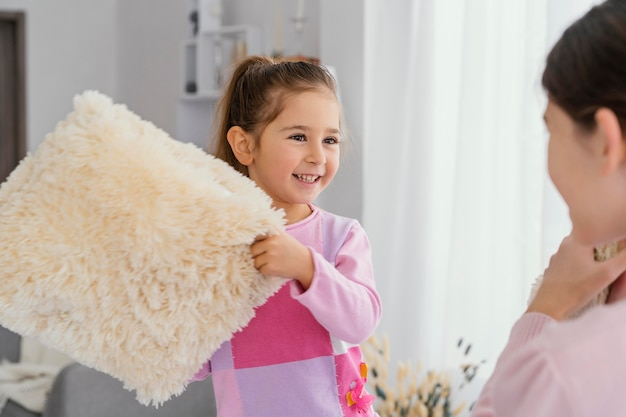 Dwie Małe Siostry Bawiące Się Poduszkami Razem W Domu Premium Zdjęcia