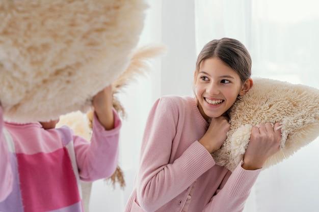 Dwie Małe Siostry Bawiące Się Razem W Domu Z Poduszkami Premium Zdjęcia