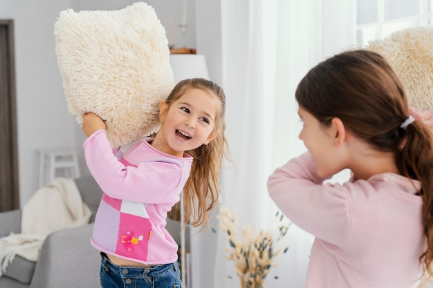 Dwie małe siostry bawiące się w domu z poduszkami