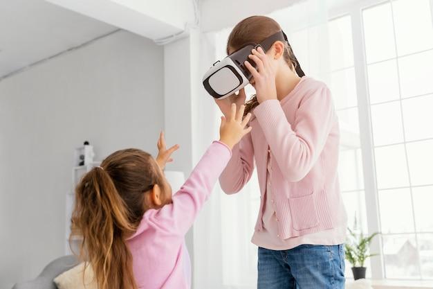 Dwie małe siostry bawiące się w domu z zestawem słuchawkowym do wirtualnej rzeczywistości