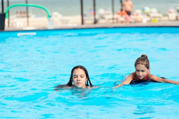 Dwie małe siostry dziewczynki pływają w dużym basenie z czystą, błękitną moją wodą w pobliżu hotelu, na tle morza i plaży. koncepcja wakacje tropikalny gorący kraj z dziećmi