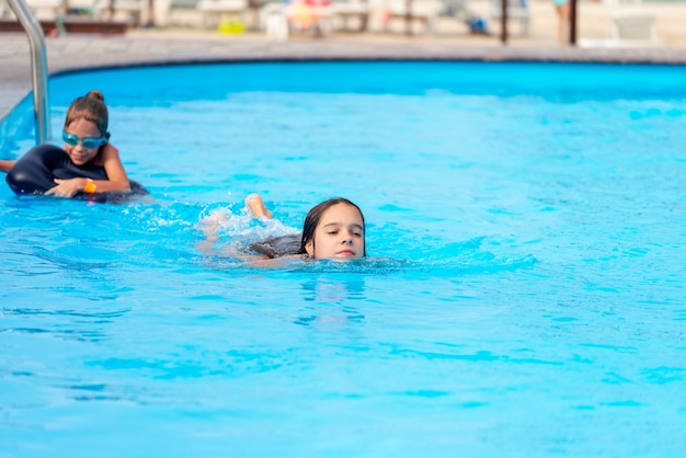 Dwie małe siostry dziewczynki pływają w dużym basenie z czystą, błękitną moją wodą w pobliżu hotelu, na tle morza i plaży. koncepcja wakacji tropikalnym gorącym krajem z dziećmi