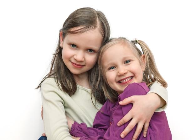 Dwie małe siostry dziewczynki przytulają się i uśmiechają na jasnym tle
