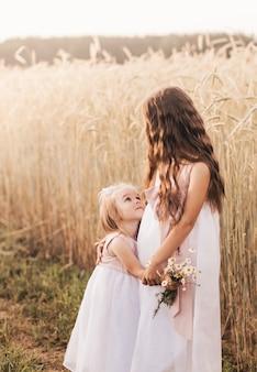 Dwie małe siostry dziewczynki przytulają się i zbierają kwiaty latem