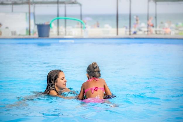 Dwie małe siostry dziewczyny pływają w dużym basenie na plaży?