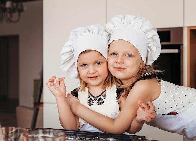 Dwie małe siostry przytulają się w kuchni w białych czapkach szefa kuchni. przezabawne dziewczyny bawią się w kuchni