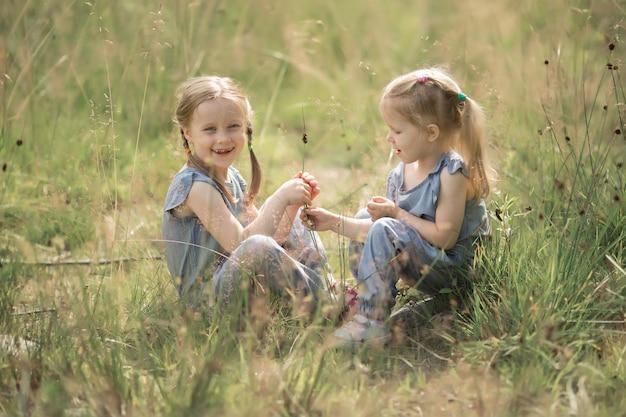 Dwie małe siostry siedzą na trawie. dziewczyny bawią się na łące