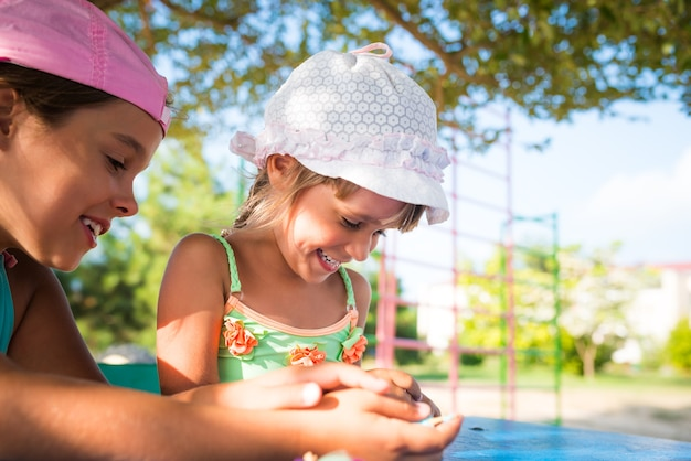 Dwie małe słodkie dziewczynki bawiące się lalkami na świeżym powietrzu, relaksując się na plaży w upalny letni dzień