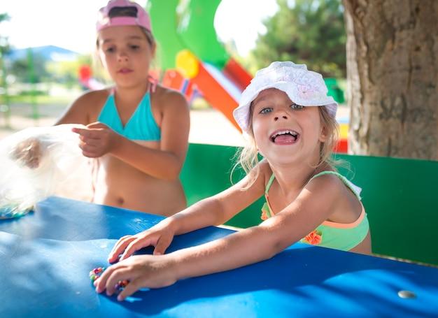 Dwie małe słodkie dziewczynki bawiące się lalkami na świeżym powietrzu, relaksując się na plaży
