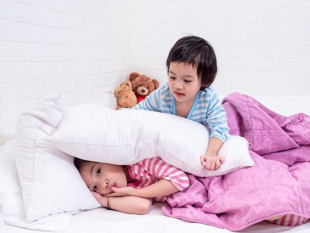 Dwie małe słodkie dziewczyny w piżamie leżące na białym łóżku. starsza siostra drażliwa młodsza siostra.