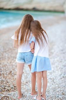 Dwie małe szczęśliwe dziewczynki bawią się razem na tropikalnej plaży