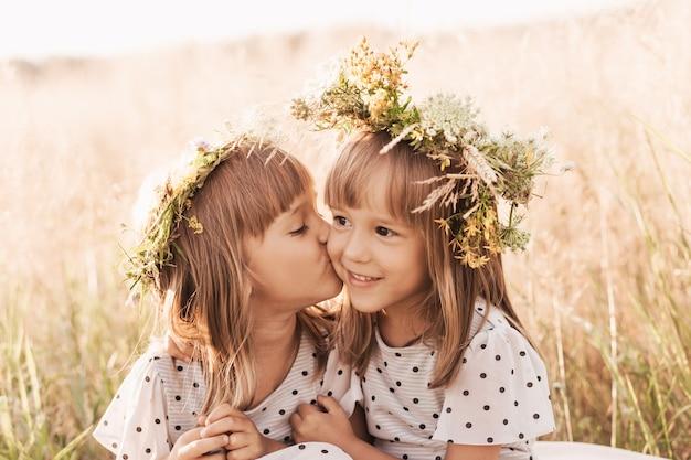 Dwie małe szczęśliwe identyczne bliźniaczki bawiące się razem w przyrodzie latem. koncepcja przyjaźni i młodzieży dziewcząt. aktywny styl życia dzieci.