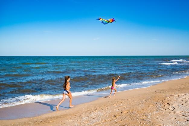 Dwie małe wesołe dziewczynki biegają z latawcem po piaszczystym brzegu nad morzem