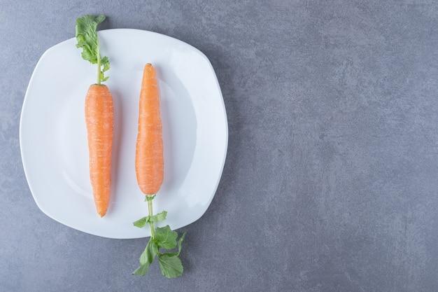 Dwie marchewki w talerzu, na marmurowej powierzchni.
