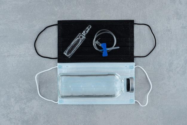 Dwie maski medyczne z medycznym etanolem na szarym tle. zdjęcie wysokiej jakości