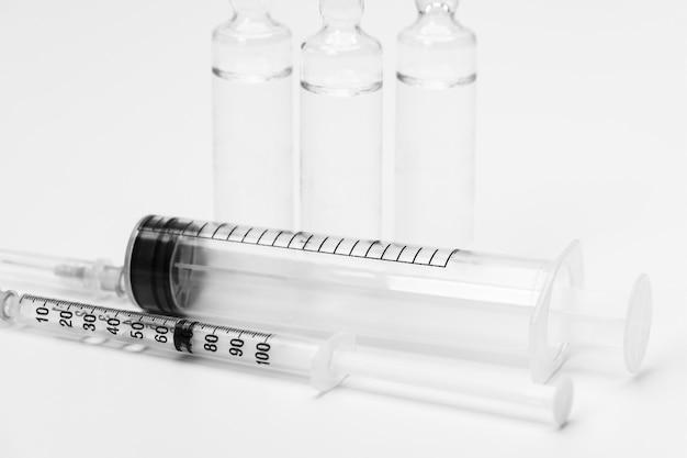 Dwie medyczne strzykawki do wstrzykiwania szczepionki i szklane ampułki ampułki ze szczepionką na białym tle