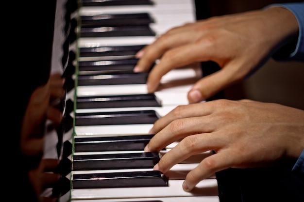 Dwie męskie dłonie na pianinie.