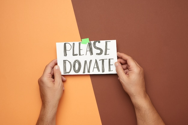 Dwie męskie dłonie trzymają kartkę papieru z napisem proszę o darowiznę