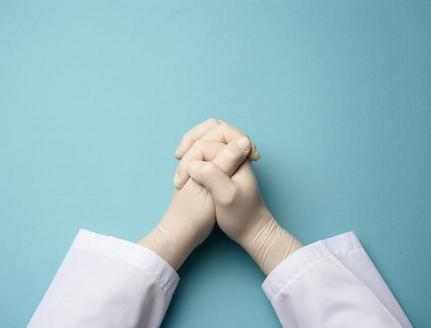Dwie męskie dłonie w białych rękawiczkach lateksowych, dłonie lekarza na niebieskim tle w pozycji modlitwy, widok z góry