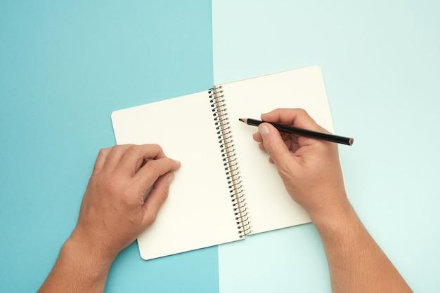 Dwie męskie ręce trzymając otwarty notatnik z pustymi białymi arkuszami, widok z góry